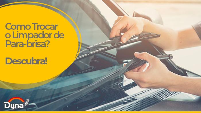 A imagem mostra mãos segurando o para-brisa de um carro.